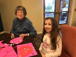 Girl Scouts and Canfield Place resident making Valentine's Day craft